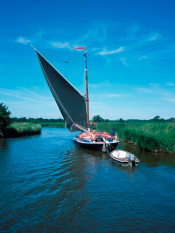 A sailing boat navigating a calm stretch of the Norfolk Broads Waterways