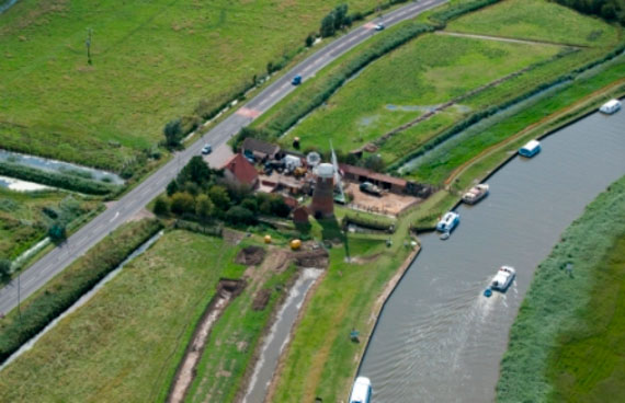 Ariel view of the windmill and buildings that make up the Stracey Arms Windpump, Tunstall. Green fields surround the buildings and pleasure boats travel along the wide stretch of water which runs past the location.
