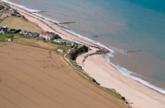Aerial view of cliff erosion at Happisburgh on the East Coast of Norfolk. The end of Beach Road and the properties there on perch perilously close to the cliff edge, protected by stone escarpments on the sandy beach below and wooden spurs out into the blue sea water.