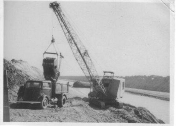 Historic image: an old drag line is pictured, emptying its contents into an old dumper truck which is parked on the lower bank of the drain.