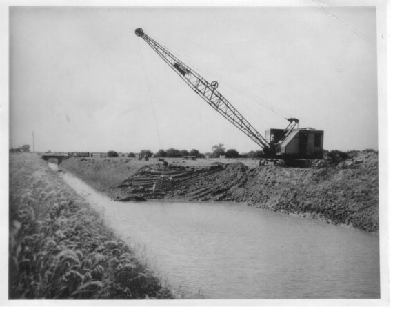 Historic image: an old dragline machine widening a drain to increase the capacity of its drainage capabilities.