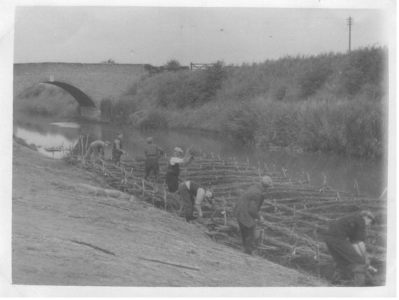 Historic image: a group of labourers using spades and scythes to manage the banks of a large drain. A brick arched bridge is featured in the background.