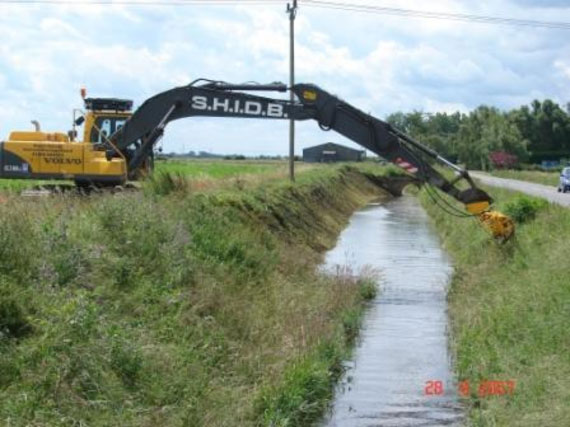 A tracked excavator uses its long-reach hydraulic arm to carry out routine weed cutting and flailing of the drain's bank sides