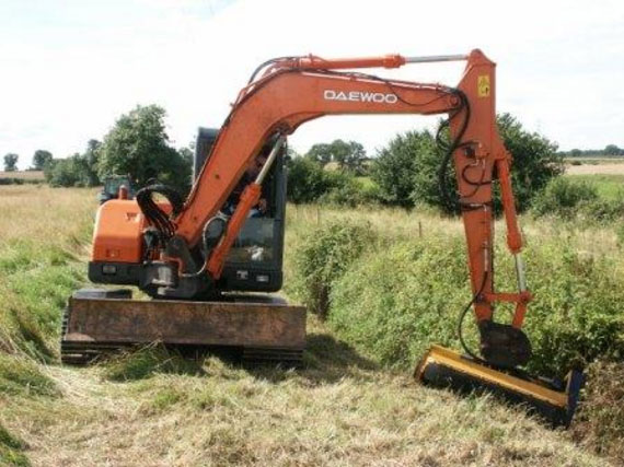 A tracked excavator uses its outreached hydraulic arm to carry out routine weed cutting and flailing of the drain's bank sides