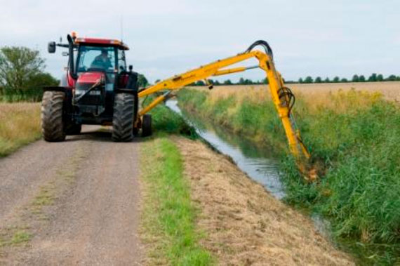 A tractor travels along a drainside road using its outreached hydraulic arm to carry out routine weed cutting and flailing of the drain's bank sides