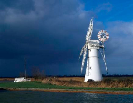A view of the Thurne Windpump, Thurne Dyke, on the Norfolk Broads, with dark storm clouds gathering over the striking white silhouette of the windmill and it's sails.