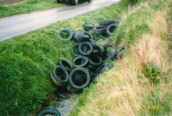Fly tipped tyres in a drainage ditch.