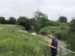 A member of the WMA team pointing at an area of floating Pennywort, a non native and invasive plant, that is found in stretches of the Cuckmere River